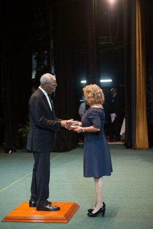H.E President David Granger hands over the Golden Arrow of Achievement for the late O'Donna Allsopp to her daughter, Susan Alsopp