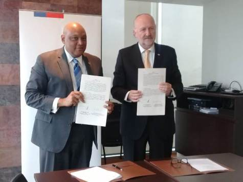 Minister of Natural Resources, Raphael Trotman and Chile's Minister of Mining, Baldo Prokurica display the MOU following the signing.