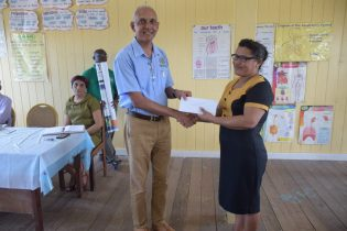 Minister of Communities, Hon. Ronald Bulkan hands over cash grant and posters to Head Teacher of Two Miles Primary, Ann Holmes