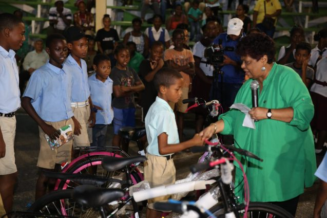 Minister of Social Protection, Amna Ally hands over a bicycle to a student
