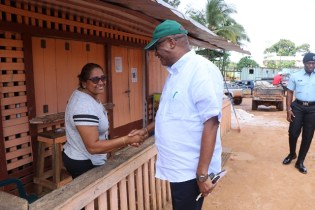 Director General of the Ministry of the Presidency, Joseph Harmon greets a resident during his visit to the Itabili community on Wednesday.