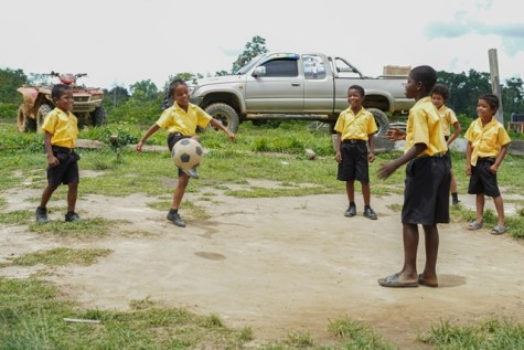 Students of Baramita village engaging in a game of football during their lunch break.