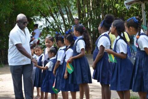 Minister of Citizenship Winston Felix, is greeted by students in Kartabo prior to his hosting a community meeting in village.