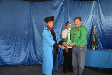 Minister of Indigenous Peoples' Affairs, Sydney Allicock handing over a trophy to one of the students.