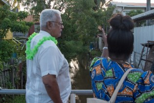Minister of Agriculture, Noel Holder, inspects a canal crossing that he assured will be desilted.