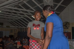 Minister of Education, Dr. Nicolette Henry shakes the hand of the girl with the best composition piece, L-Dee Johnson.
