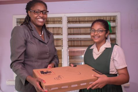 Minister of Public Service, Tabitha Sarabo-Halley presents Region 6 NGSA top student Chitra Ramdihal with a laptop