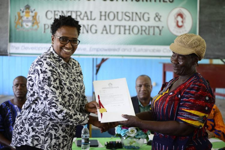 Minister of Communities, with responsibility for Housing, Hon. Annette Ferguson hands over a land title to a resident