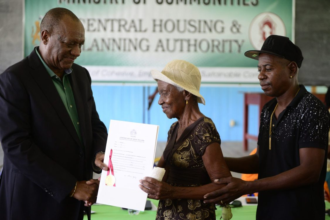 This grandmother is relieved, after decades of wait, to finally receive her title for her land from the Director-General of the Ministry of the Presidency, Joseph Harmon
