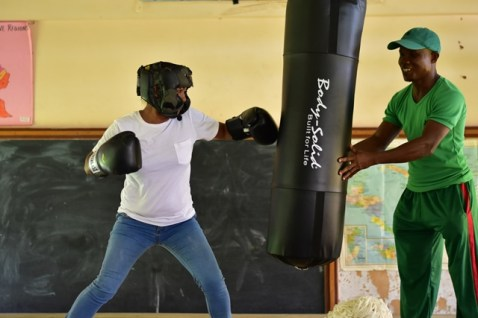 Boxing Coach Orlan Rogers holds the punching bag while Suzika France takes a few swings.
