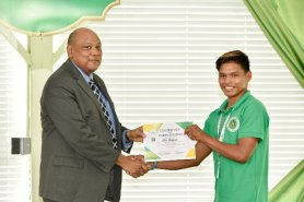 Minister of Natural Resources, Mr. Raphael Trotman presents a certificate of participation to Mr. Elon Benjamin.