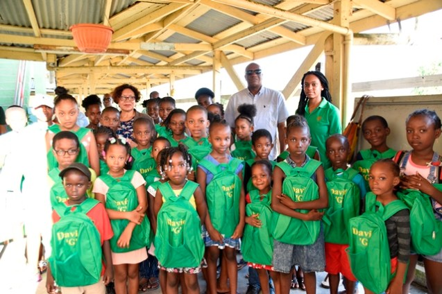 Minister within the Ministry of Indigenous Peoples' Affairs, Hon. Valerie Garrido-Lowe and Director General of the Ministry of the Presidency with children from the Stanleytown community who were gifted David 'G' School bags.