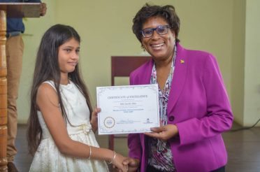 Minister of Public Telecommunications, Hon. Catherine Hughes presents a certificate to a participant, during Coding Camp graduation ceremony
