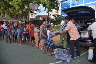 His Worship the Mayor of Georgetown, Pandit Ubraj Narine hands out school supplies.