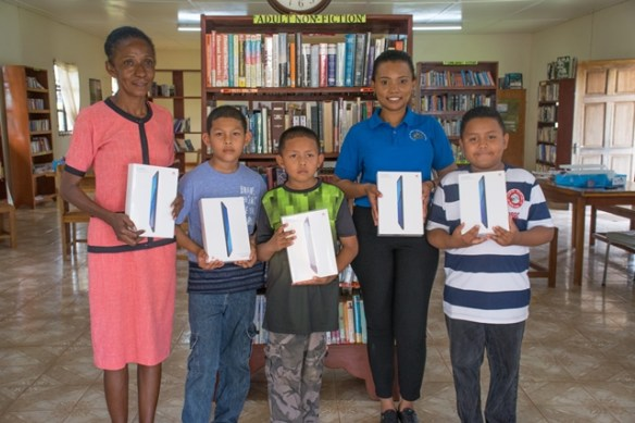 Deputy Librarian, Andrea Charles along with a Ministry of Public Telecommunications representatives and youths of Lethem with the donated electronic tablets.