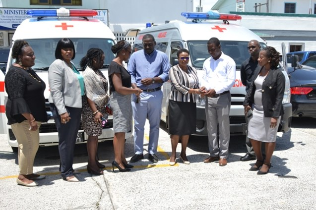 Minister of Public Health, Hon. Volda Lawrence hands over the key of the ambulance to Region 4's RHO, Dr. Quincy Jones while Director of Primary Healthcare Services, Dr. Ertenesia Hamilton hands over the keys to the ambulance to Region 3's RHO, Dr. Cerdel McWatt.