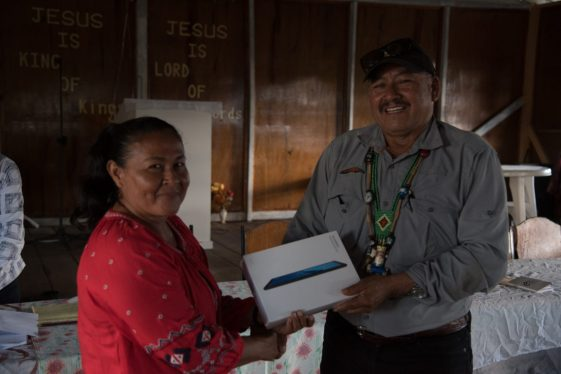Mother of Jerohn Conelius, Wanita Corenlius of Imbaimadai Village receives a tablet from Minister of Indigenous Peoples' Affairs, Hon. Sydney Allicock