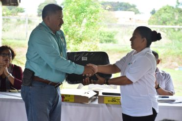 Minister of Indigenous Peoples Affairs, Sydney Allicock, who was attending a special meeting of Indigenous Community leaders, assisted in handing out a REDD+ Guyana package to Jacqueline Allicock, NRDDB's Chairperson