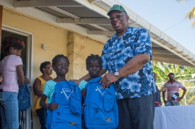 Minister of Finance, Hon. Winston Jordan hands over school bags filled with supplies to children from the Seafield/Tempe Neighbourhood