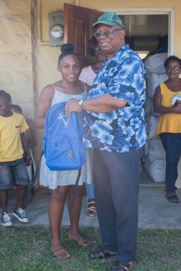 A teen from the Seafield/Tempe Neighbourhood receives her backpack with supplies form Minister Jordan