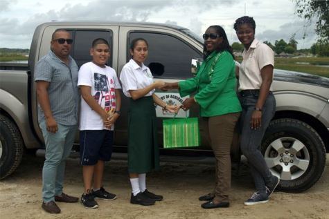 Riana Toney flanked by her father and brother receives her gift from Minister within the Ministry of Agriculture, with responsibility for Rural Affairs, Hon. Valerie Adams-Yearwood.