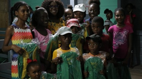 Minister of Foreign Affairs, Hon. Karen Cummings pose with recipients of some David G school bags following a community meeting at the Rosignol Primary School