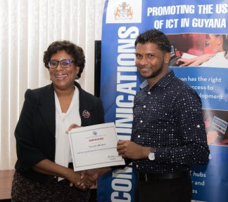 Minister of Public Telecommunications, Hon. Catherine Hughes, hands over a certificate to Rimalio Persaud for participating in the National Capacity Building on Web Accessibility program.
