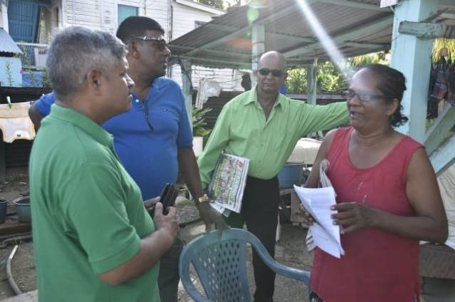 Minister within the Ministry of Public Infrastructure Jaipaul Sharma with residents of Bath Settlement.