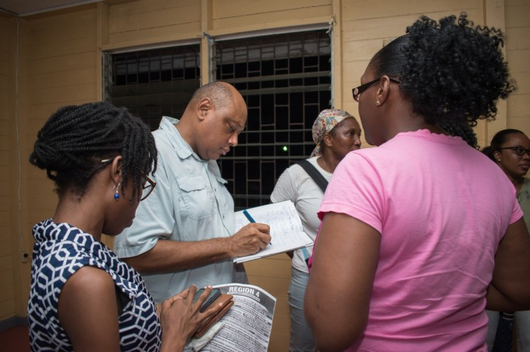 Minister of Natural Resources, Hon. Raphael Trotman noting residents' concerns at the Camp Town Community Centre on Sunday