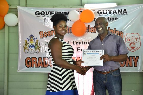 Minister within the Ministry of Social Protection Keith Scott hands over a certificate of completion to one of the participants of the BIT boat building training exercise