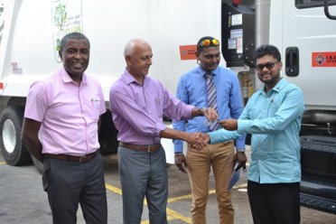 Minister of Communities, Hon. Ronald Bulkan hands over the keys to the new garbage truck to His Worship the Mayor of Georgetown, Pandit Ubraj Narine.