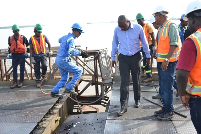 Minister of Public Infrastructure, Hon. David Patterson inspects the steel loosened plates on the bridge.