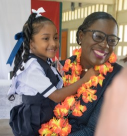 Minister of Education, Hon. Dr. Nicolette Henry with St. Aloysuis Primary student.