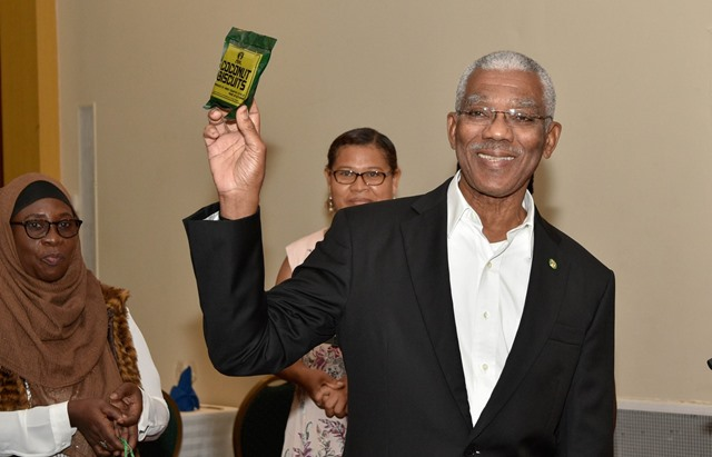 President David Granger holds a pack of coconut biscuits locally made while at the Guyana Manufacturing and Services Association business luncheon.
