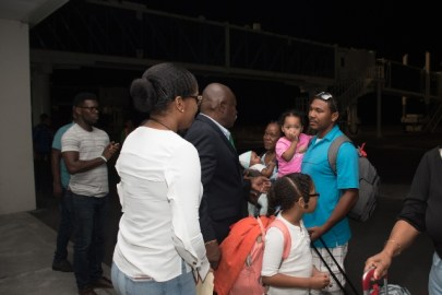 Minister of Citizenship, Hon. Winston Felix greets Orin Grimmond and his family as they disembark the aircraft.