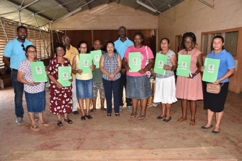 Minister of State, Hon. Dawn Hastings-Williams and Commissioner and Chief Executive Officer (CEO), Guyana Lands and Surveys Commission, Trevor Benn along with residents of Matthew's Ridge who received their titles.