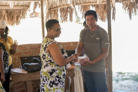 Minister of Public Health l, Hon. Volda Lawrence hands of some of the sport equipment to Toshao of the Monkey Mountain Village, Lincoln Singh.