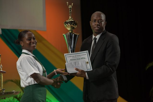 District Education Officer, Sherwin Blackman presents CAPE 2019 Top Performer, Shanomae Milling with her award.