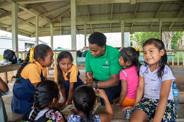 Minister within the Ministry of Communities, with responsibility for Housing, Hon. Annette Ferguson chatting with children in Kopinang, Region 8.