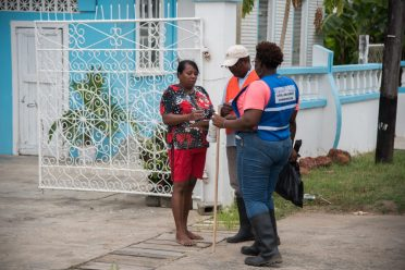 [In the photo, from left to right] A resident of Rebecca's Lust, Sandra Ramson accepts cleaning supplies from members of the Civil Defence Commission (CDC).