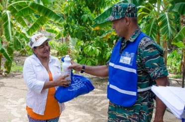 Lieutenant Lakshman Persaud, Operations Officer donating supplies to affected resident.