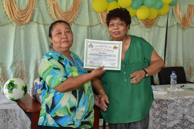 Minister of Social Protection, Hon. Amna Ally presenting a certificate to one of the Hinterland Employment and Youth Service (HEYS) participants.