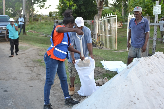 A CDC volunteer assisting residents in Region 5 to fill the sandbags.