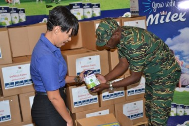 De Sinco Limited's Brand Manager, Aisha D' Abreu handing over the relief items to Director-General of the CDC, Lieutenant Colonel Kester Craig