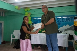 Ministerial Advisor and Member of Parliament, Hon. Mervyn Williams handing over a certificate to one of the beneficiaries.
