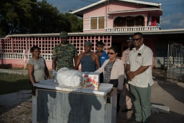 Minister of State, Hon. Dawn Hastings-Williams, Civil Defence Commission and Regional Information Officer, Ganesh Mahipaul hands over hamper to residents of Zeelught.