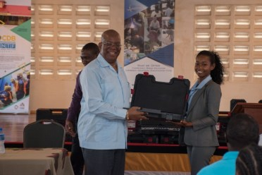Finance Minister, Hon. Winston Jordan hands over one of several training kits to beneficiary Onika Bobb.