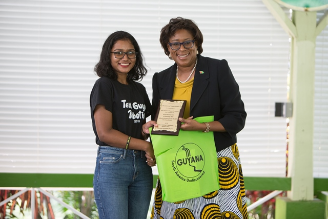 Minister of Public Telecommunications, Hon. Catherine Hughes hands over awards to one of the STEM Guyana group members.