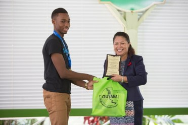Minister of State, Hon. Dawn Hastings-Williams, hands over awards to one of the STEM Guyana group members.