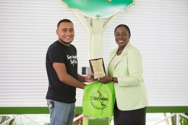 Minister of Education, Hon. Dr. Nicolette Henry, hands over awards to one of the STEM Guyana group members.